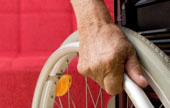 Man's hand on wheelchair rim in front of a red couch.