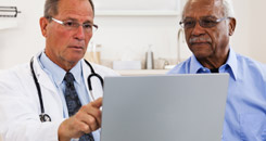 Male doctor and patient talking and looking at a laptop.