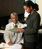 woman reading a notepad standing next to a doctor sitting at a desk