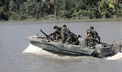 Soldiers are in a boat near a jungle area that could have been sprayed with Agent Orange