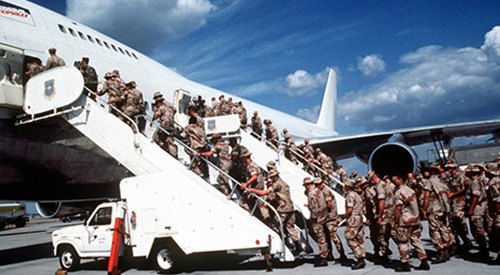 Soldiers boarding a commercial jet.