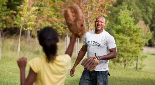 Man in Air Force t-shirt and his daughter playing catch
