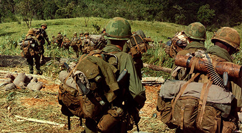 Vietnam soldiers marching in full gear, descend a hill in Vietnam.