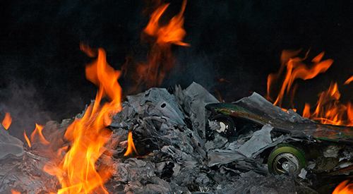 A fire burning debris and garbage.