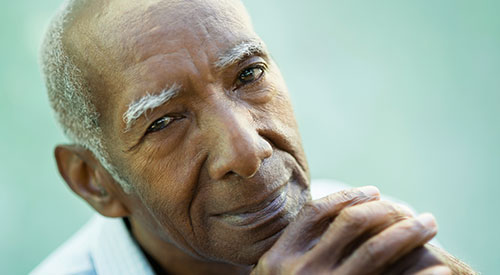 Older African American man smiling with his chin resting against his hands.
