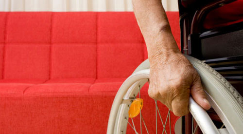 Man's hand on rim of wheelchair in front of a red couch.