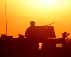 Silhouette of a soldier on a truck in front of the bright sun
