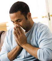 A man is sick with the flu and blowing his nose