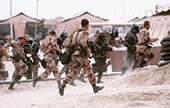 Soldiers run to a bunker as part of an air raid drill during Operation Desert Storm.