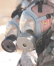 Two servicemembers wearing gas masks