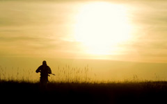 Silhouette of a soldier in front of the bright sun