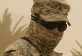 Soldier in goggles and camouflage fabric face covering in the desert