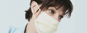 Employee Health: Closeup photo of a medical professional with a surgical mask over her face