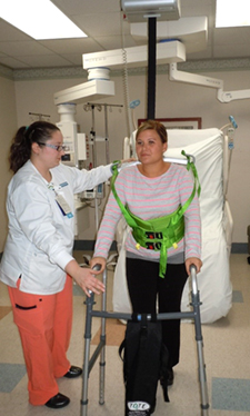A nurse is using a ceiling lift to support a patient walking