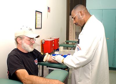 A veteran has his blood drawn by a doctor.