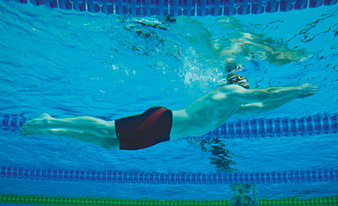 male swimming in swimming lane