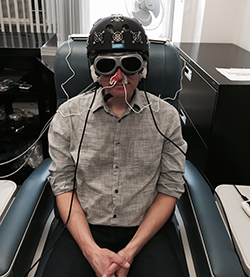A man demonstrates equipment, including an LED helmet, intranasal diodes, LED cluster heads placed on the ears, and goggles.