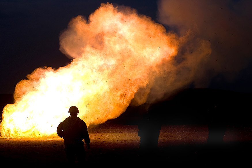 A soldier stands in silhouette against a large flame from the disposal of mortar charges.