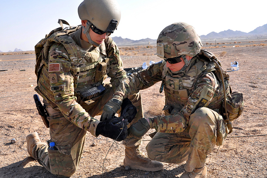 Two U.S. soldiers in full uniform tape a detonation cord during explosives training in a desert.