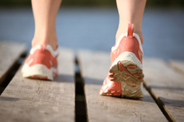 Feet in athletic shoes walking on a boardwalk