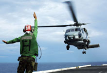 Man directing a helicopter landing on an aircraft carrier