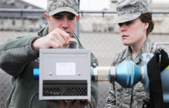 Two airmen with a radiation detection instrument