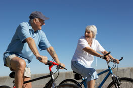 An older couple riding bicycles outside