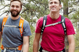 Two young men backpacking through the forest