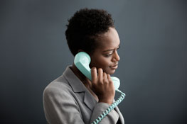 a woman dialing 1-855-QUIT-VET on her blue corded phone