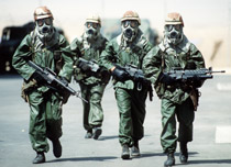 Four soldiers wearing gasmasks and protective gear