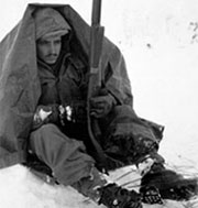Soldier sitting in the snow under a blanket in the Chosin Reservoir